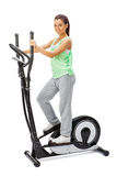 Young woman uses elliptical cross trainer. Young woman uses elliptical cross trainer Royalty Free Stock Images