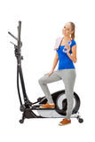 Young woman uses elliptical cross trainer. Stock Image
