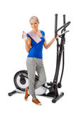 Young woman uses elliptical cross trainer. Stock Photography