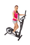 Young woman uses elliptical cross trainer. Royalty Free Stock Image