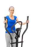 Young woman uses elliptical cross trainer. Royalty Free Stock Photos
