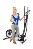 Young woman uses elliptical cross trainer. Stock Photo