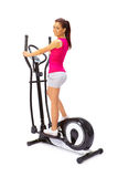 Young woman uses elliptical cross trainer. Young woman uses elliptical cross trainer Stock Image