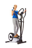 Young woman uses elliptical cross trainer. Royalty Free Stock Photo