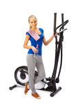 Young woman uses elliptical cross trainer. Royalty Free Stock Images
