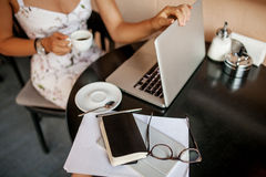 Young woman uses laptop in cafe Royalty Free Stock Images