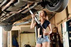 A girl uses oil drainer for a lifted car. A young woman uses oil drainer for a lifted car Royalty Free Stock Photography