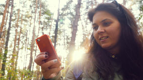 Young woman uses the phone in the autumn forest stands through the sun Royalty Free Stock Photo