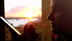 Young woman uses the phone, standing at the window drinking coffee on the background of a beautiful sunset with sun stock video