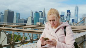 A young woman uses a smartphone. Brooklyn Bridge in New York, urban background. With skyscrapers stock footage