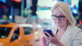 A young woman uses a smartphone on a busy street in Manhattan against the backdrop of bright advertising lights, yellow stock image