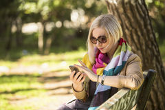 Young  woman uses smartphone sitting on bench in the Park. Royalty Free Stock Images