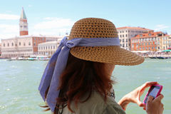 Young woman uses the smartphone to send a picture in Venice Ital Stock Photo