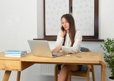 Young woman uses smartphone while working from home