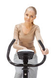Young woman uses stationary bicycle trainer. Royalty Free Stock Photos