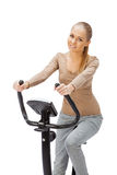 Young woman uses stationary bicycle trainer. Royalty Free Stock Image