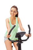Young woman uses stationary bicycle trainer. Stock Photos