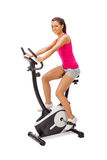 Young woman uses stationary bicycle trainer. Royalty Free Stock Images
