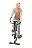 Young woman uses stationary bicycle trainer. Stock Photography