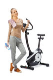 Young woman uses stationary bicycle trainer. Stock Photo