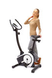 Young woman uses stationary bicycle trainer. Stock Images