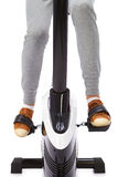 Young woman uses stationary bicycle trainer. Royalty Free Stock Photo