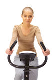 Young woman uses stationary bicycle trainer. Stock Image
