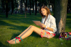 Young Woman Uses Tablet PC In The Park royalty free stock image
