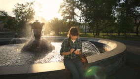 A young woman uses a telephone near the fountain at sunset. A young woman in a plaid shirt playing a game or communicating with friends using an app in a white stock footage