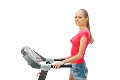 Young woman uses treadmill. Royalty Free Stock Photography
