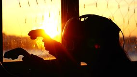 Young woman uses a virtual reality glasses at home during sunset with city background from the window and beautiful stock footage