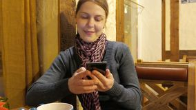 Young woman using app on a phone and drinking coffee and smiling in cafe. 4K UHD stock video footage