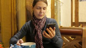 Young woman using app on a phone and drinking coffee and smiling in cafe. 4K UHD stock video