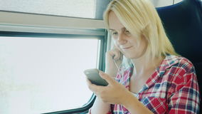 A young woman is using app on a smartphone. Goes by train, sits near the window stock footage