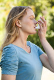 Young woman using asthma inhaler at park Royalty Free Stock Image