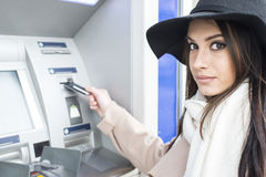 Young woman using the ATM Royalty Free Stock Photos