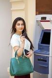 Young woman using an automated teller machine Royalty Free Stock Photos