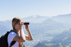 Young woman using binoculars during an hike. Young woman using binoculars on top of a mountain during an hike with mountains and valleys in the background Royalty Free Stock Images
