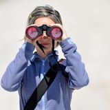 Young woman using binoculars outdoor Stock Image