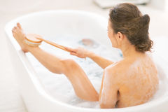 Young woman using body brush in bathtub Royalty Free Stock Photo