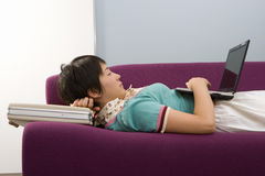 Young woman using briefcase as pillow on sofa, using laptop computer, profile. Young women using briefcase as pillow on sofa, using laptop computer, profile Stock Image