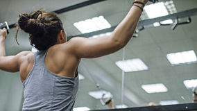 Young woman using a cable pulley machine in the gym Stock Photography