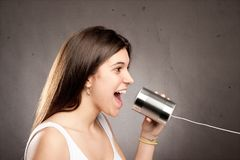 Young woman using a can as telephone. On a gray background Stock Photo