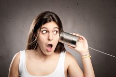 Young woman using a can as telephone. On a gray background Royalty Free Stock Photos