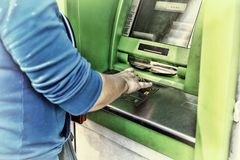 Young woman using a cash point. Young girl using ATM Royalty Free Stock Photo