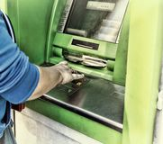 Young woman using a cash point. Young girl using ATM Royalty Free Stock Photography