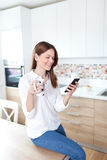 Young woman using cell phone in the kitchen Stock Photography
