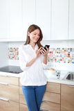 Young woman using cell phone in the kitchen Stock Photos