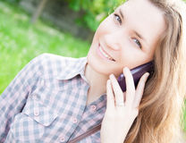 Young woman using cell phone outdoors Stock Photo