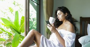 Young Woman Using Cell Smart Phone Drink Coffee Happy Beautiful Girl Chatting Online Over Big Window With Tropical. Garden View Slow Motion 60 stock footage